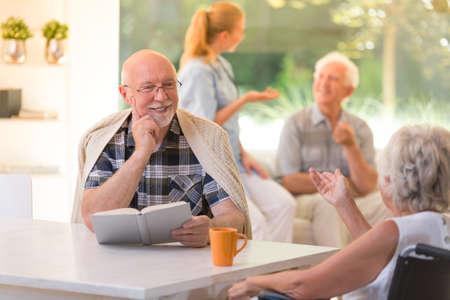 Homme souriant avec des lunettes tenant un livre et de parler à la femme dans fauteuil roulant Banque d'images - 89250267