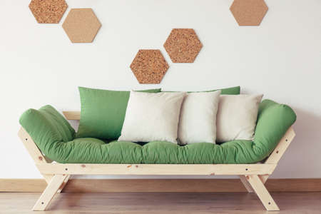 Grey pillows on green wooden sofa against white wall with natural cork