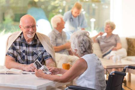 Verheiratetes Paar von Ältesten, die zusammen sitzen und alte Fotos im Pflegeheim aufpassen