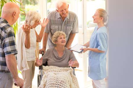 Joven enfermera diciendo adiós a la mujer mayor que sale del hospital con sus hermanos