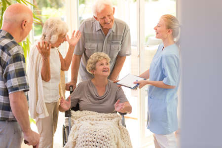 Young nurse saying goodbye to elder woman leaving hospital with her siblings Banco de Imagens - 89250368