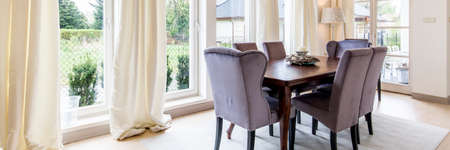 Calm bright dinning area with few windows, table and chairs Stok Fotoğraf - 87819991