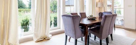 Kalm helder eetgedeelte met enkele ramen, tafel en stoelen