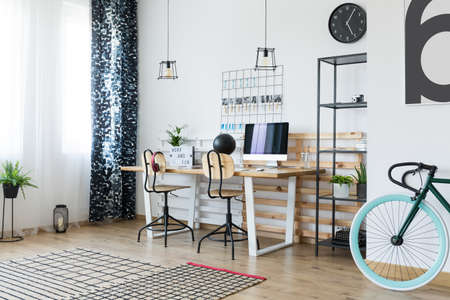 Bike with blue wheel in multifunctional workspace with patterned carpet and clock on white wall