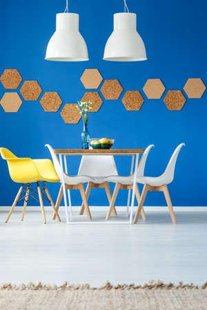 水色の壁上の環境に優しいデザイン要素のあるダイニング ルームで黄色の椅子とテーブルの上の白いランプ
