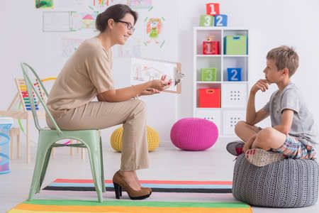 Young boy is sitting on a grey pouf in front of his psychotherapist in a room with colored carpet Stock Photo