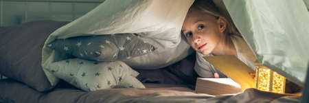 Mysterious girl hiding under the covers with book and torch Stok Fotoğraf