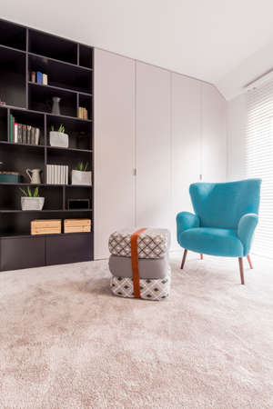 Cozy looking blue chair standing next to three cushions strapped with a leather belt in the middle of a monochromatic day room