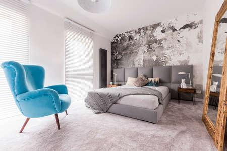 Comfortabele, blauwe stoel in een slaapkamer die naast een tweepersoonsbed met kussens staat, en een wolfsstandbeeld dat op een nachtkastje staat en wordt weerspiegeld in een gigantische spiegel Stockfoto