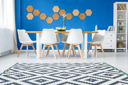 白い家具と青の壁に天然コルクのモダンなリビング ルームの北欧カーペット 写真素材