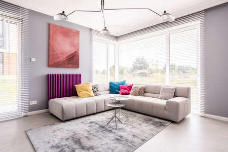 Dwa stoliki stojące na miękkim, szarym dywanie przy sofie w rogu salonu i abstrakcyjny obraz na ścianie