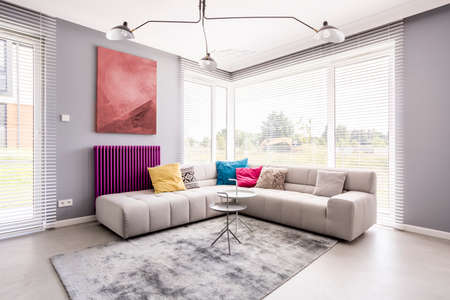 Two small tables standing on a soft, grey carpet by the sofa in the corner of a living room and an abstract painting on the wall Stockfoto