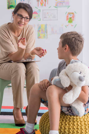 Boy is holding stuffed toy and is looking at pedagogue during therapeutic meeting in classroom Stok Fotoğraf - 87823360