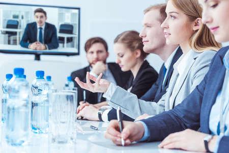 ビデオ会議中に投資家との交渉でポイントを作る若い女性