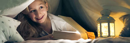 Young cheerful little girl hiding under the covers reading book Stock Photo