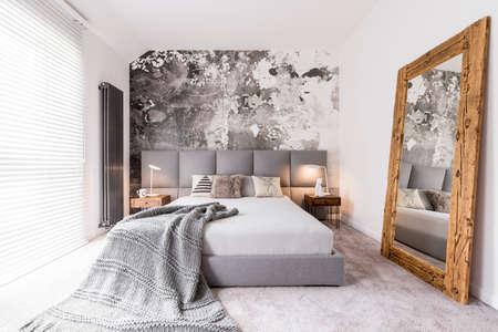 Lange deken op een tweepersoonsbed in een rechthoekige, monochrome slaapkamer met een radiator naast een raam met blinds