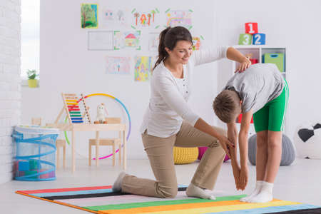 young boy in gymnastic costume during posture correction lesson in colorful classroom