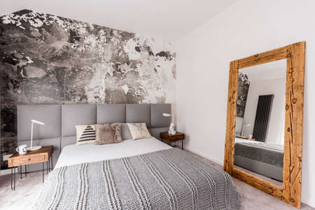 Grey king-size bed in a spacious bedroom with an abstract wallpaper on the wall, and a large, wood framed mirror Stock Photo