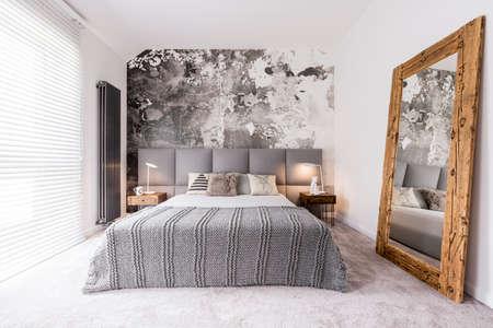 壁によって支えられる木のフレームの鏡に反映される優雅な、単色の寝室 写真素材
