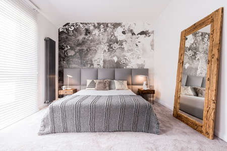 Elegant, monochromatic bedroom reflected in a wood framed mirror supported by the wall Фото со стока