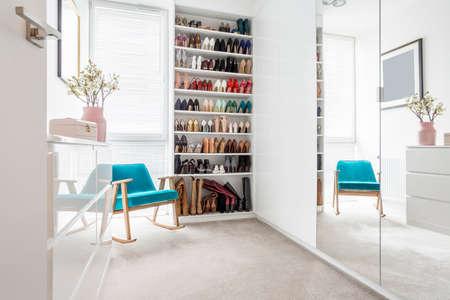 Ampio guardaroba di scarpe accanto a una sedia blu, comoda e comoda, in piedi nella stanza bianca di una donna
