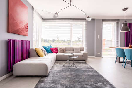 Abstract painting hanging above a purple radiator, and a large sofa with many, colorful pillows in a stylish living room Banco de Imagens - 87807328