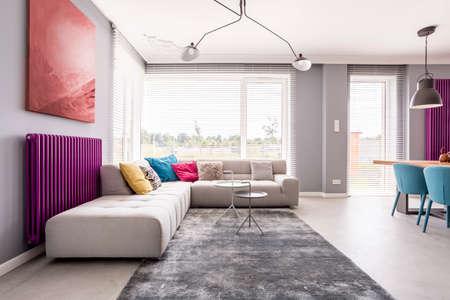 Malarstwo abstrakcyjne wiszące nad chłodnicą purpurową i dużą sofą z wieloma kolorowymi poduszkami w stylowym salonie