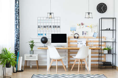 Black and white patterned carpet in monochromatic home office with photos and plants Stock Photo