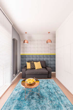 Small cozy bedroom with a black comfortable bed, large blue carpet lying on the wooden floor, and a small table with a bowl of lemons Reklamní fotografie