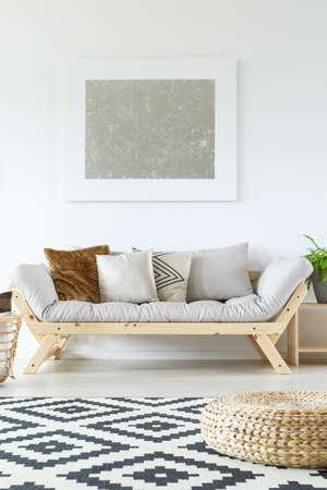 Umsponnener Puff auf Schwarzweiss-Teppich im Wohnzimmer mit silberner Malerei über braunem Kissen auf grauem Sofa Standard-Bild - 87663453