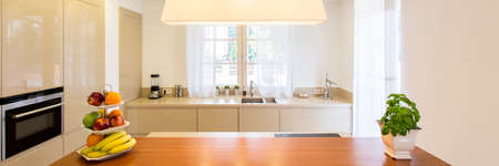View of the kitchen island with fruits and herbs and worktop at window