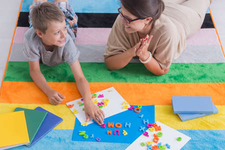 Smiling teacher and child lie on a colorful carpet and play during school activities