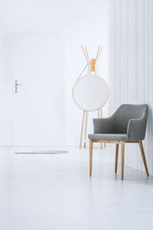 Minimalistic design of modern entrance with white door, tube wall, and simple gray chair Imagens