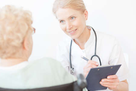 Smiling young doctor with stethoscope looking at older women before surgery