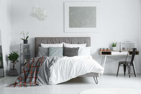 Red and grey, checkered bedsheets lying on a king-size bed in a minimalist bedroom