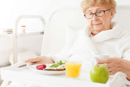 Elder eating healthy meal at hospital which consists of an apple and orange juice Banco de Imagens