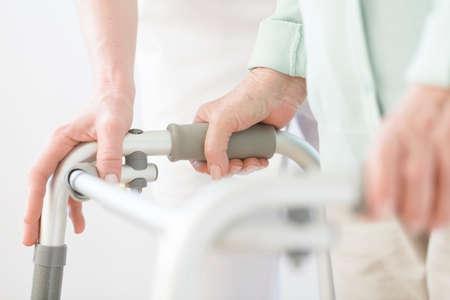 Close-up van oudere persoon met behulp van rollator tijdens revalidatie in het ziekenhuis