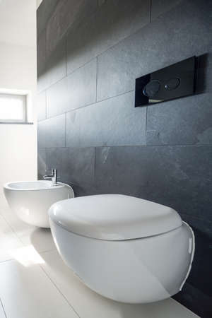Badkamerhoek met verdraaide tegels aan de muur, wit toilet en urinoir
