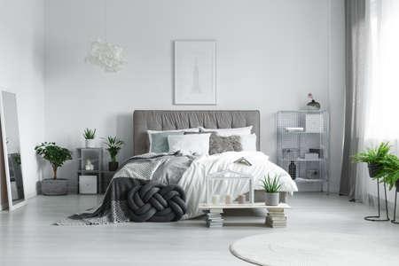 植物で満たされた寝室のキングサイズのベッドの上に横たわる多くの枕