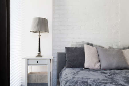 Bedroom corner with bedside cabinet, lamp and marital bed