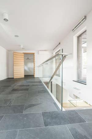 Ruime gang met trappen, houten deur en tegels op de vloer Stockfoto