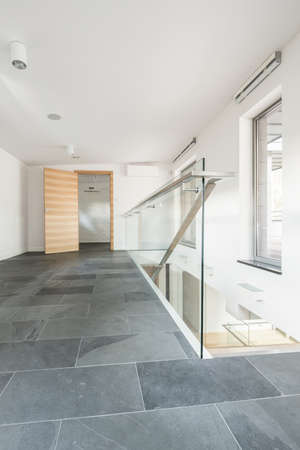 Spacious corridor with stairs, wooden door and tiles on the floor Imagens