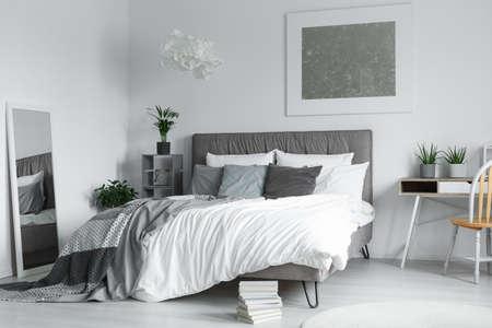 하얀 카펫 옆에 바닥에 누워있는 작은 은닉 물과 큰 거울에 반영된 다양한 베개가있는 더블 침대