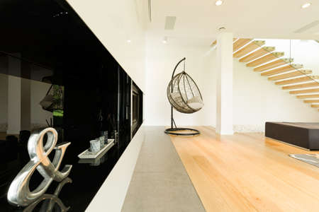 House corner with black design and modern armchair on a parquet