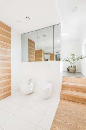 Badkamersbinnenland met toilet, urinoir, grote spiegel en houten ontwerp