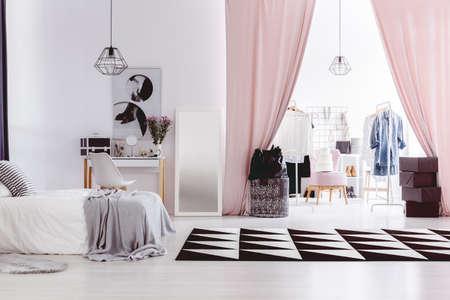 Zwart en wit tapijt in de slaapkamer van de vrouw met inloopkast naast een kaptafel Stockfoto