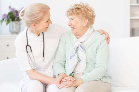 Smiling senior woman in sweater sitting on white sofa during meeting with happy doctor