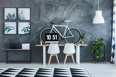 White chairs at the table with monitor and bike in workspace interior with geometric carpet on the floor and posters on concrete wall