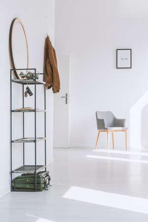 흰 벽과 밝은 아파트 입구 근처에 간단한 회색 안락 서 서