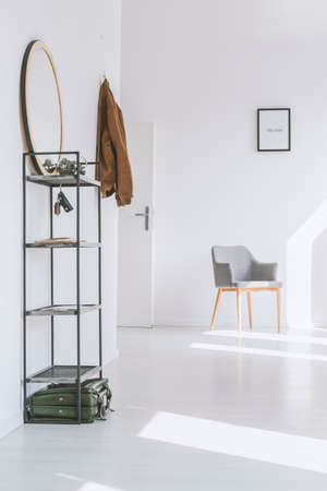 Simple gray armchair standing near the entrance to a bright apartment with white walls